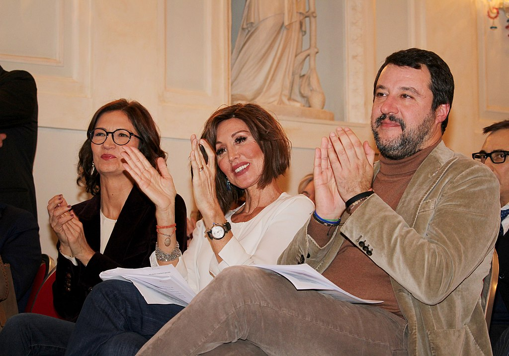 Matteo Salvini wearing a tan cord jacket and trousers and darker tan rollneck is seated next to a woman in a white blouse and another woman wearing spectacles, a white blouse and a jacket. All three in the row are white with dark hair and aged around 40 years. They're clapping. The room that they are in is marble and white plaster with carvings that look like they're from the Renaissance period or just after partially visible on the walls
