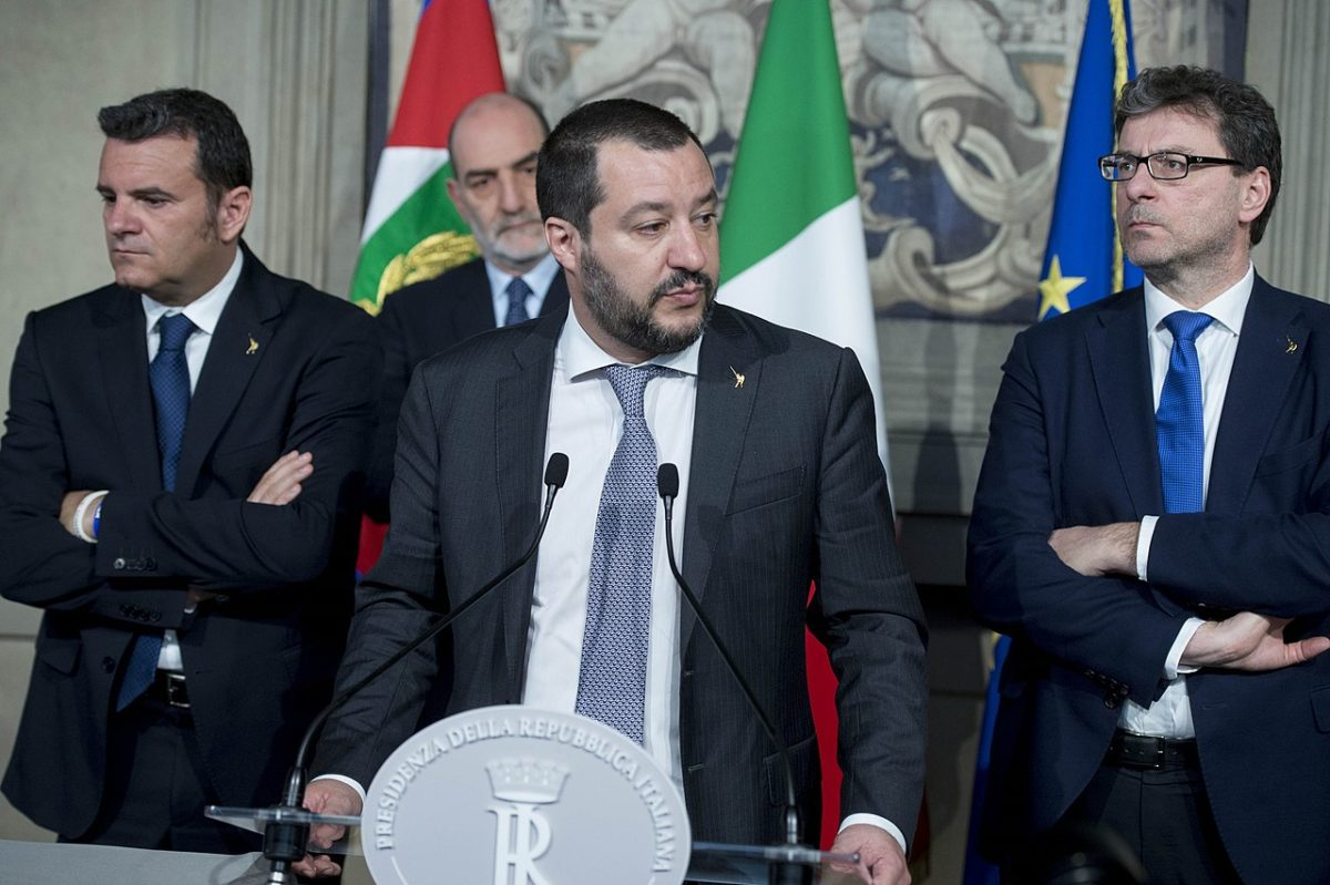 Matteo Salvini stands at an official Italian government lectern giving a speech. He wears a dark grey suit and lighter grey tie, with a white shirt. He is flanked by two men who are similarly attired with another male figure stood behind them. part of a stone carved statue can be seen behind them alongside several Italian tricolors and an EU flag