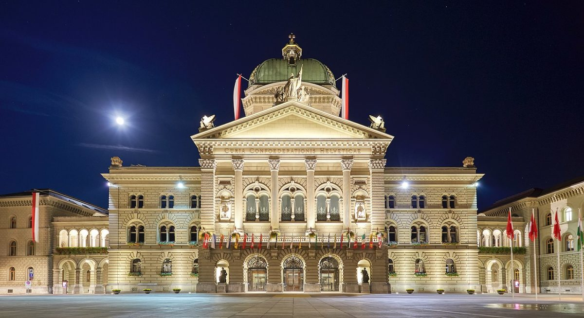 Federal Palace of Switzerland with full flags due to Indian President's state visit. Plaza view during full moon with clear night sky.
