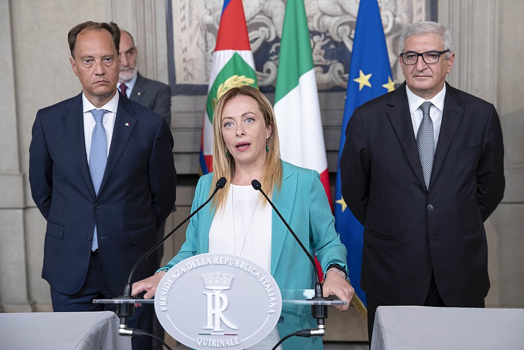 Giorgia Meloni (a white woman in her early 40s) stands in front of a podium. She is wearing a teal coloured jacket and a white blouse. She is flanked by two white middle aged men probably in their 50s both of whom wear suits and ties. An Italian flag and an EU flag hang upright on poles behind them