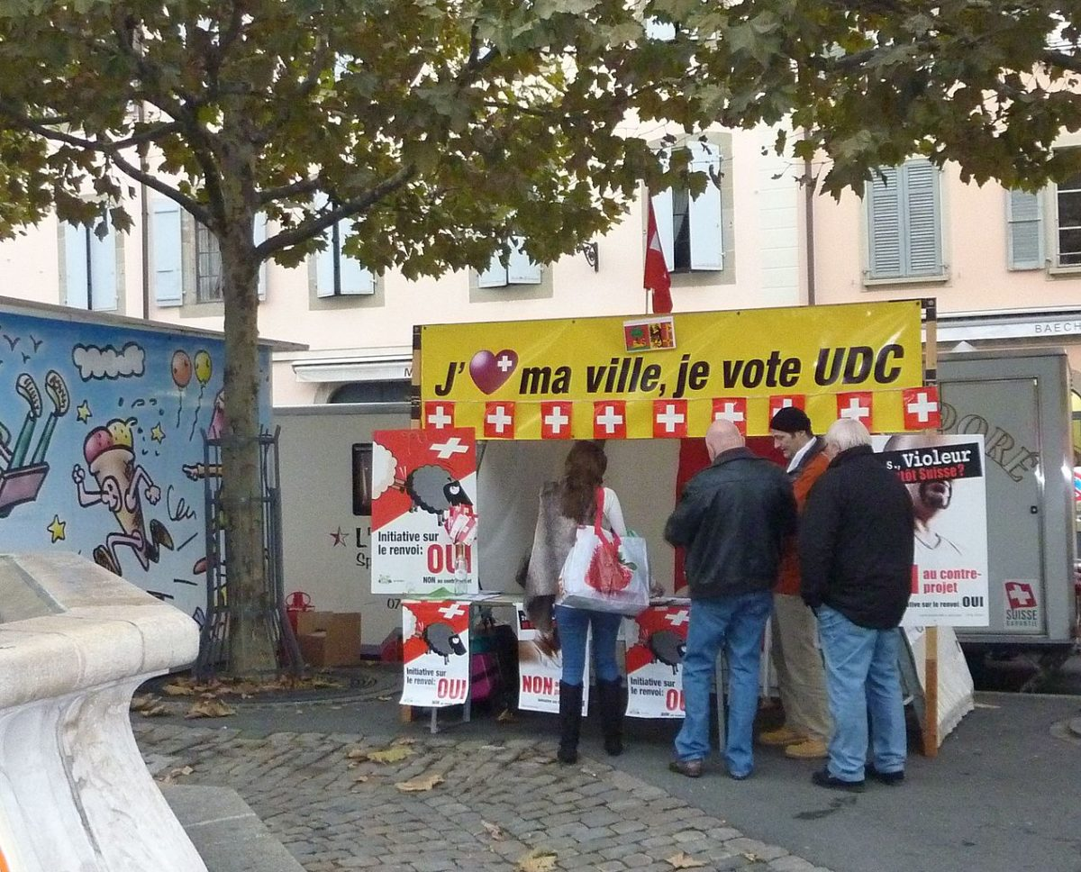 Street stand for the Swiss people's Party. A group of middle aged white people, affluent looking, all men apart from one woman, stand with their backs to the camera deep in discussion. They stand at the side of a small town square under some trees on an early autumn day, in front of a market stall style stand bearing Swiss flags and Swiss People's Party posters