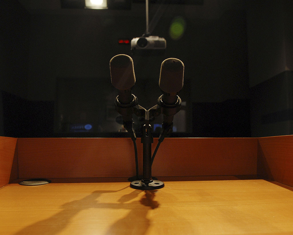 Close up of two darkly coloured microphones on a wooden podium. They are looking out into a darkened auditorium, where a projector is just about visible. the primary light source in the space is shining on the podium so that is illuminated whereas the rest of the auditorium is dark