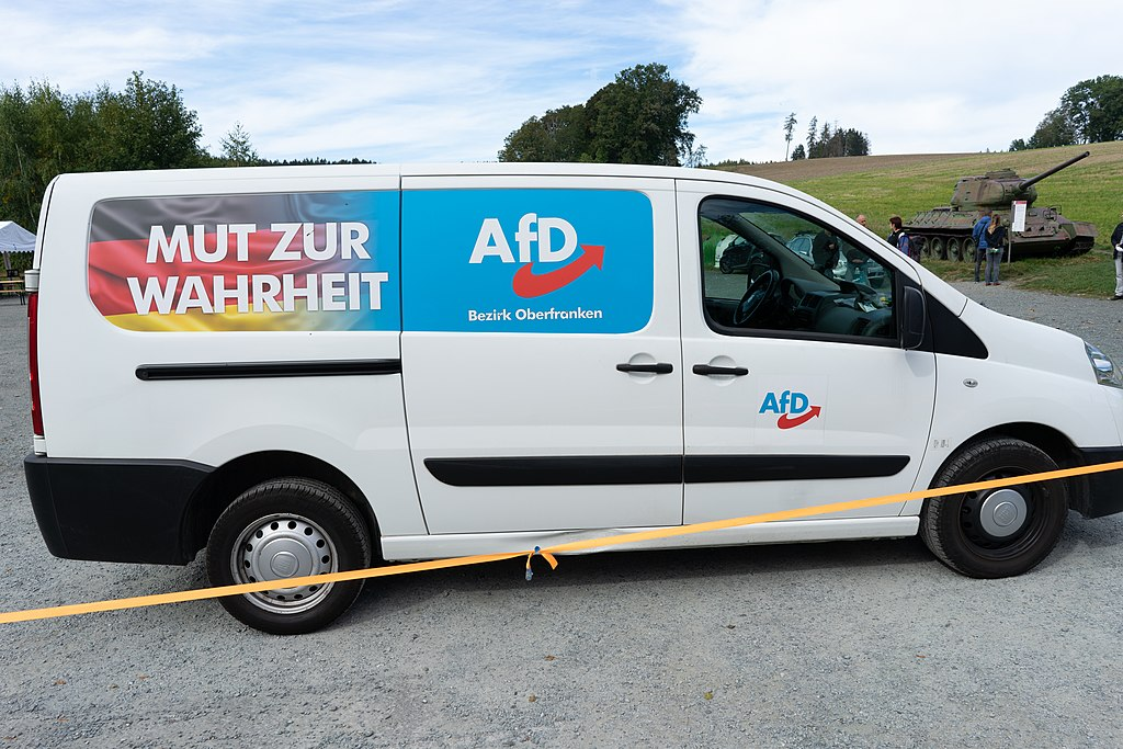 Alternative for Germany political party campaign van. The van is medium sized, painted white, has the party's name logo and a small amount of German language text printed on the side. It is parked at some kind of park or rural location, with lightly wooded hills in the background. A few people stand looking at an old military tank with an information plaque which is parked on the grass besides the gravel surface car park where the van is sited. This indicates some kind of war memorial or small scale military museum location