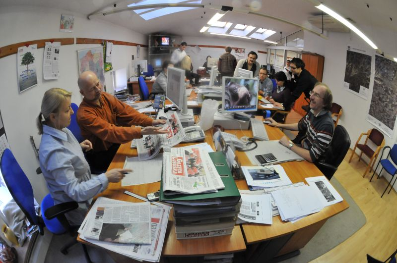 A group of informally dressed middle aged white people are working in an office. It is high up in a roof space and illuminated y skylights. The office is sparsely furnished, although the central desk wwhere many of the workers sit or stand around flatscreened computer monitors is quite crowded with papers and units like intrays and filining systems where paper is stored. It is the office of a local newspaper in Poland