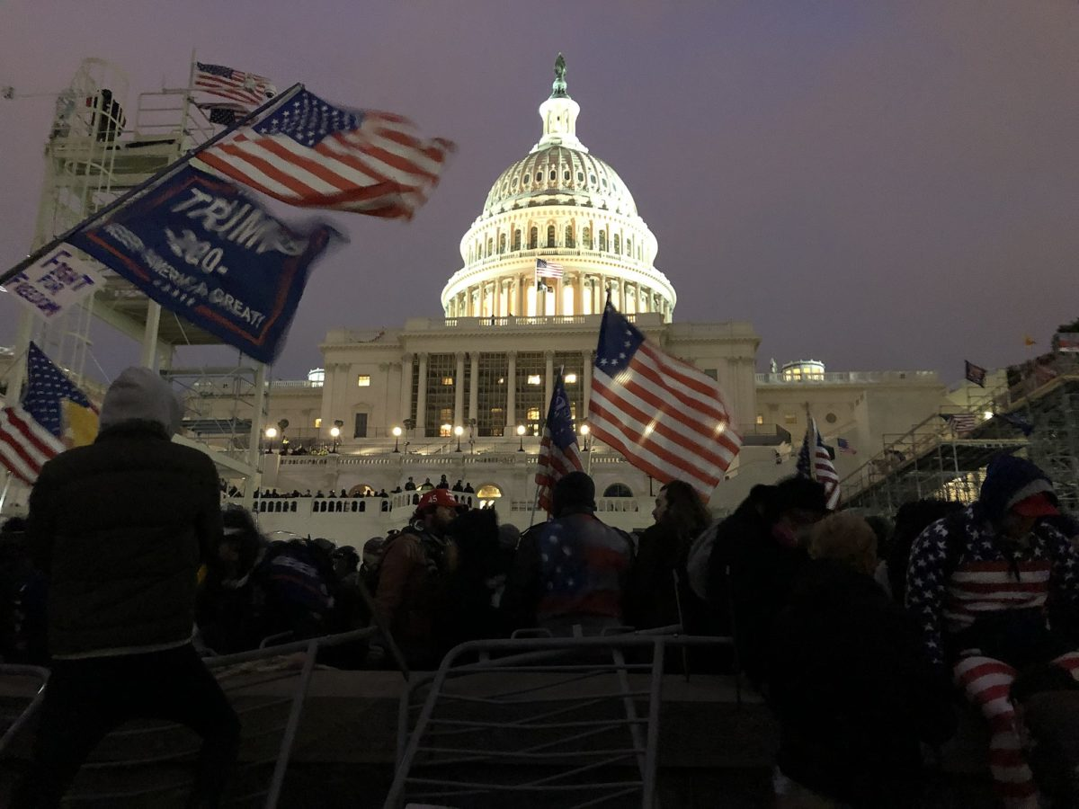 US Capitol Building at dusk. The dome of the building is illuminated in the centre of the image. In the foreground protestors in winter clothing many waving Trump flags, and flags representing the early flag of the United States c. 1785 are flying. A large crowd is assembled stretching up to building which is barricaded with crowd control barriers. A group can be seen on the building's terrace, it's not clear if these are soldiers/police or protestors