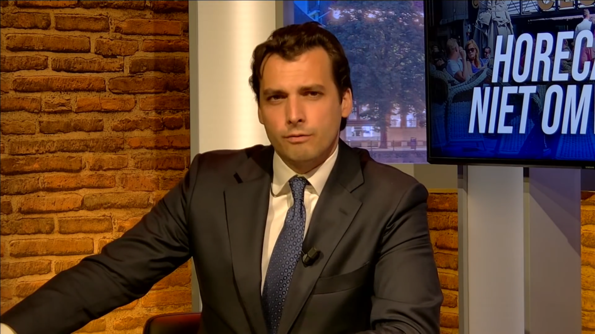 Picture of Thierry Baudet taken in 2020. Thierry Baudet is a thin white man in his 30s wth black slicked back hair. He wears a shiny charcoal coloured suit, a white shirt and a blue tie. He is seated in front of a window and a brick wall, with half a TV screen in the background. This give it the feel of being either a TV studio or some kind of seminar event