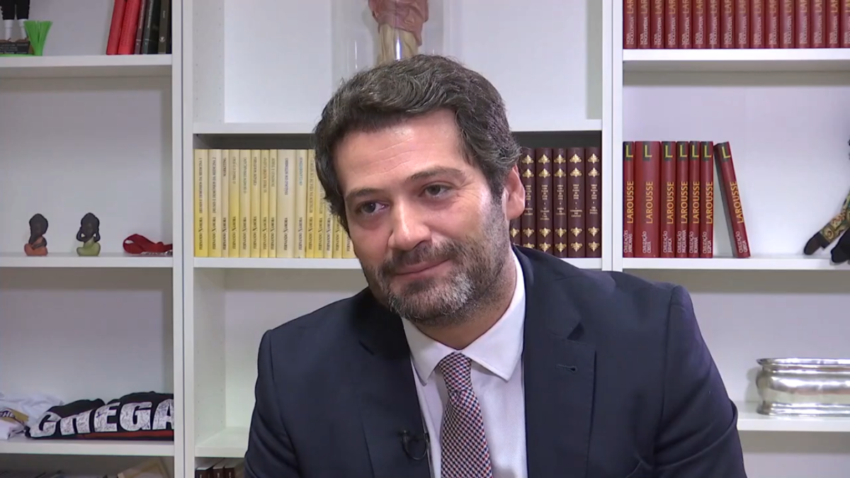 Picture of Chenga (Enough!) party leader André Ventura. He is a white man in his late 30s with greying mid-coloured brown hair, a short greying beard of the same complexion and is seated in front of a bookcase which contains several rows of books organised by series and some knickknack type items including a folded Chenga t-shirt. He is wearing a navy/black coloured suit jacket, white buttoned up shirt and a salmon coloured tie