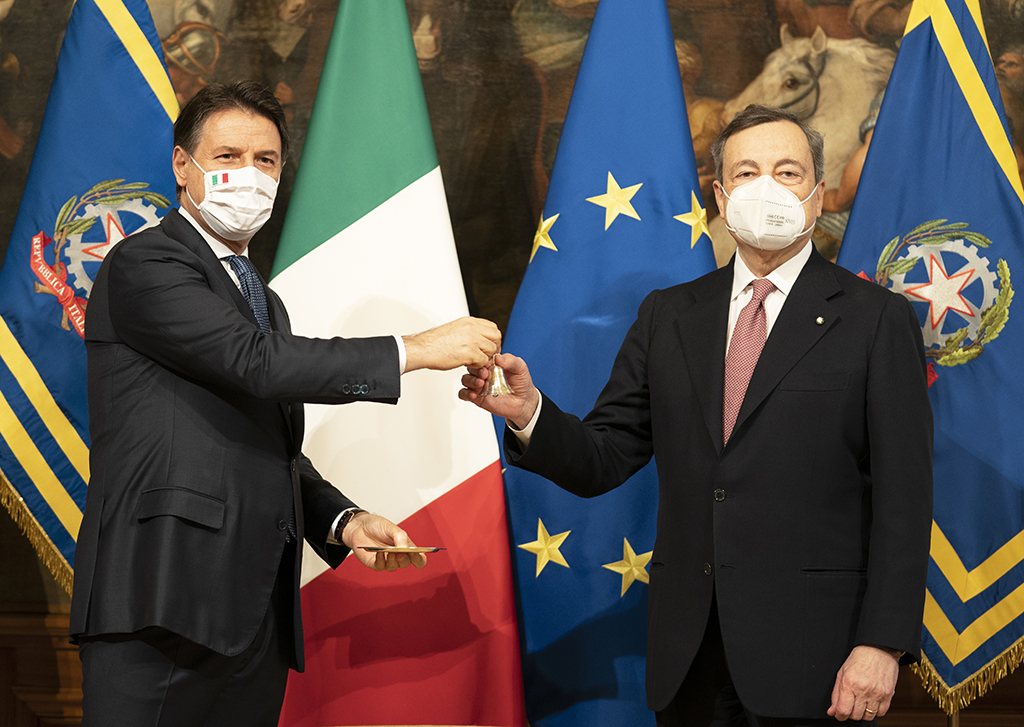 Giuseppe Conte hands Mario Draghi the Italian Cabinet Bell used to facilitate and officiate meetings. They are both white mean wearing suits, clean shaven, with short dark hair. Both wear white facemasks with the Italian flag in their corner. They stand in front of a row of Italian tricolor, European Union and flags bearing the insignia of the Italian Republic, behind which a monumental painting can be observed featuring horses and mounted soldiers