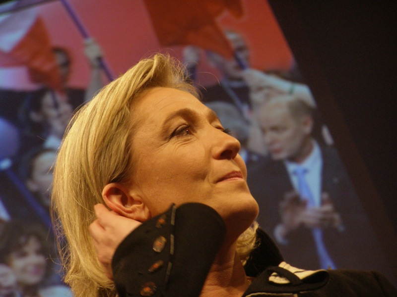 Close up of Marine Le Pen on a podium in profile. Behind her a crowd of white men in suits, who appear to be party delegates are projected onto a screen. Some of them hold partially visible French tricolors. The bulk of the frame is Marine Le Pen a middle aged white woman with blond hair who is wearing a black business type suit