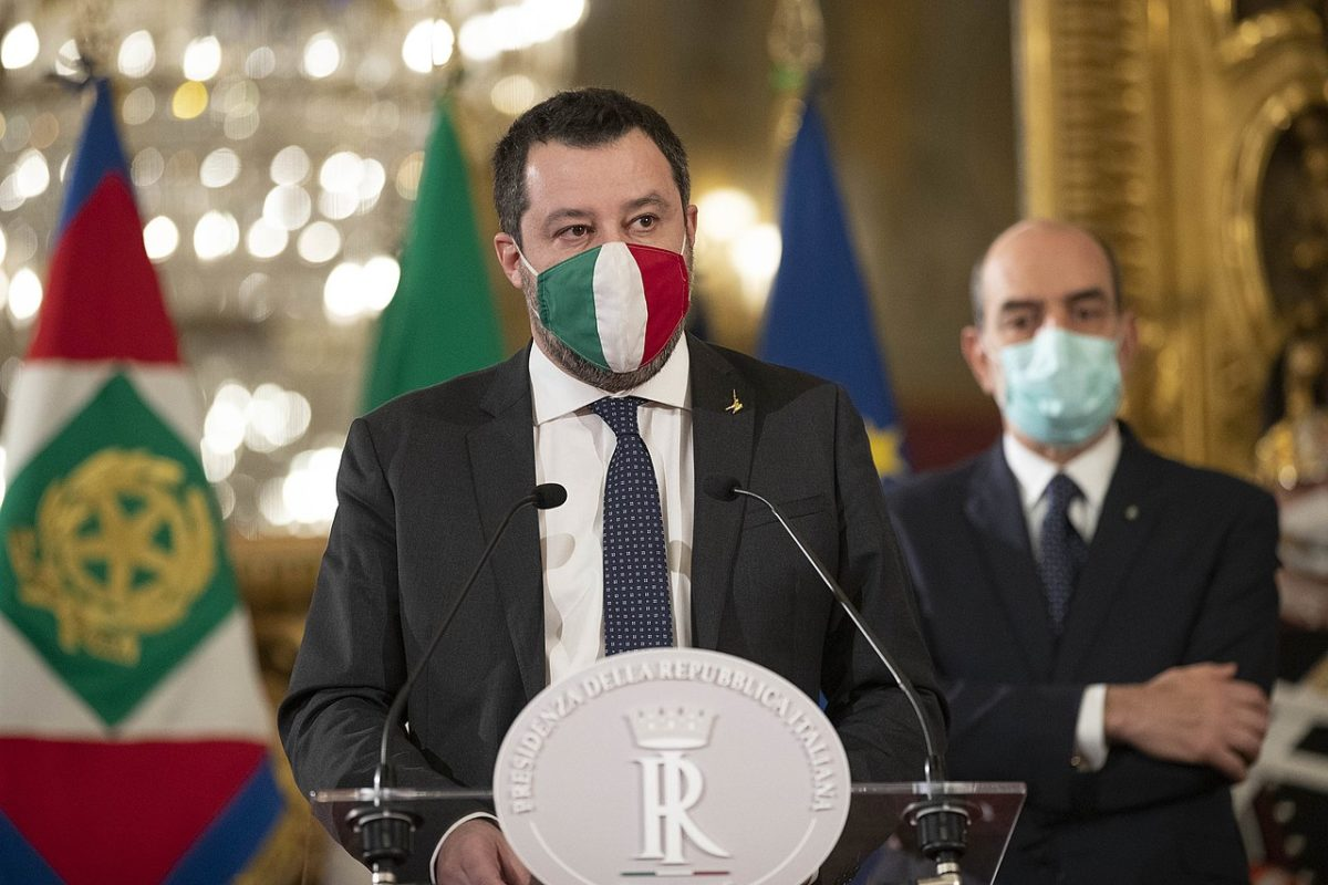 Matteo Salvini stands at a lectern indoors, with a logo of the Italian republic emblazoned in silver in front of the battery of microphones mounted on the podium. He is a white man in his late 40s with short dark, straight dark brown hair. A short beard can be glimpsed beneath the facemask he wears which is in the colours of the Italian tricolor. He wears a dark grey suit, a white shirt and a dark blue tie. Flags and another middle aged man, also in a suit and wearing a surgical blue/green facemask can be seen behind him