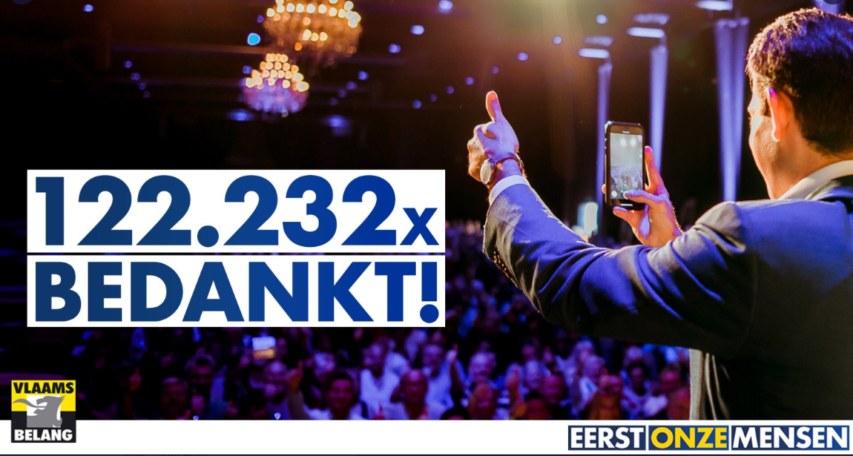 Vlaams Belang social media graphic. Shows party leader Tom van Grieken upon the occasion of his election as party leader in 2019, viewed from behind giving a thumbs up to the crowd in a ballroom at his election celebration. He holds a smartphone in his other hand which is in it's camera mode. The image is overlayed with Dutch language text thanking the 122,000+ people who voted in the election. The border contains party logos and slogans