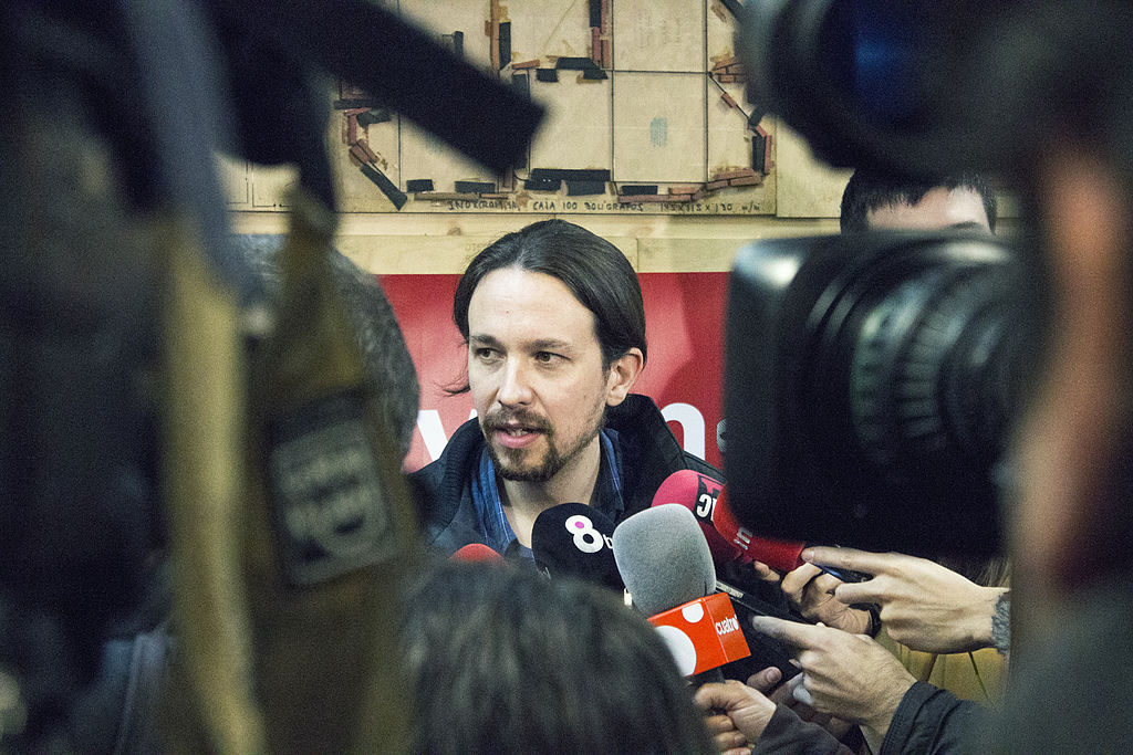 Photo depicts Pablo Iglesias the former leader of Podemos. He is in the centre of the frame stood in front of a wall with a red banner on it surrounded by a bank of TV boom mics, TV cameras, reporters hands holding hand held mics and press photographers wielding DSLRs. His head and shoulders are visible. He is a short, slight white man in his late 30s with long dark hair tied in a pony-tail and a a short dark beard covering all of his face. He is dressed in navy blue and black as if for cold/wet weather
