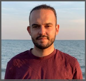 Profile picture of Mattia Zulianello. He is a white man in his 30s with dark hair pulled back and a short full, dark beard. He is stood on a beach at twilight with the sea behind him and wears a claret coloured t-shirt.