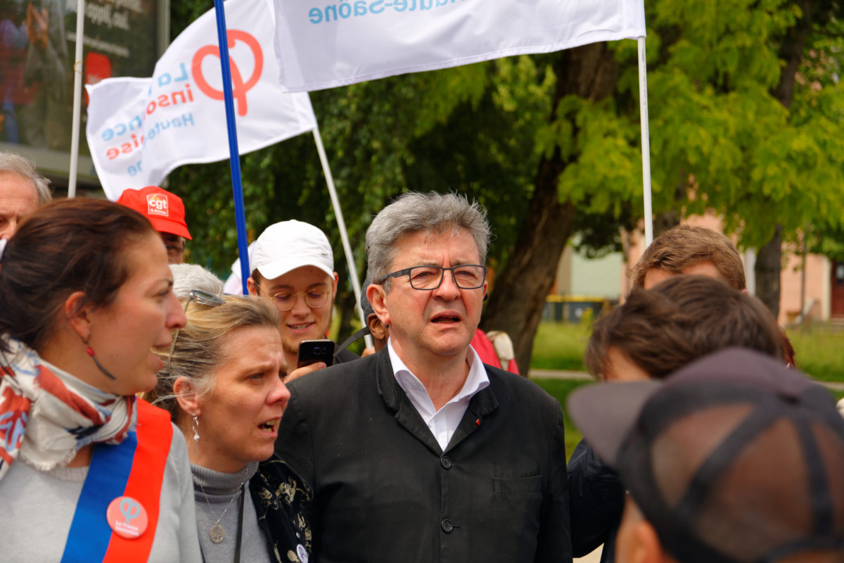 Jean-Luc Mélenchon is depicted amidst a group of striking workers. The striking workers are a range of ages, mostly younger white women, and are stood outside on a sunny day holding flags representing their trade union as if picketing or at a rally. Jean-Luc Mélenchon is stood the centre of the frame. He is a white man in late middle age with largely white and grey hair, clean shaven with glasses. He wears an open neck white shirt and a largely buttoned up workers' style jacket in black with a couple of small pin badges on the lapel